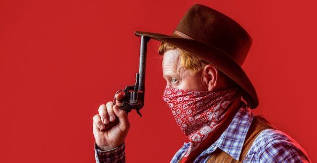 모자에 카우보이의 초상화입니다. 카우보이 모자를 쓰고 남자의 총. 카우보이의 초상화입니다. 웨스트, 총