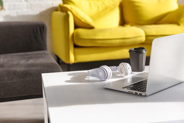 Портрет уютной стильной меблированной комнаты с чашкой кофе, наушниками и портативным компьютером, лежащим на столе