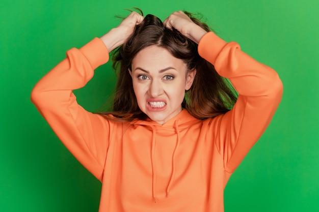 미친 화난 성가신 여성의 초상화는 녹색 배경에 머리카락을 찢는다