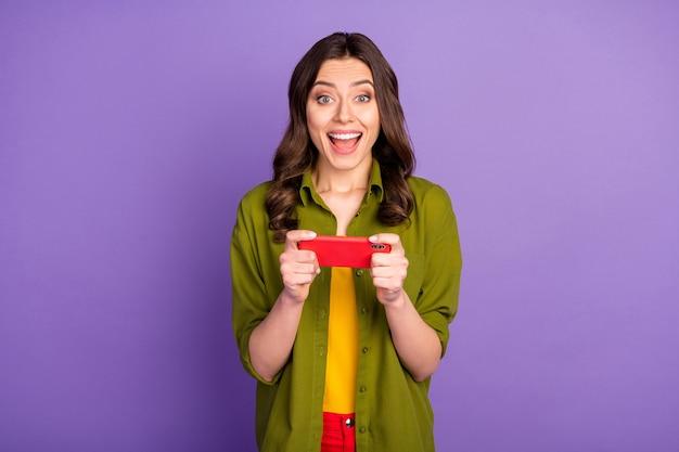 クレイジーな驚愕の少女の肖像スマートフォンを使用するビデオソーシャルメディアゲームに感銘を受けた高速接続悲鳴すごいomg着用格好良い服孤立した紫色の背景