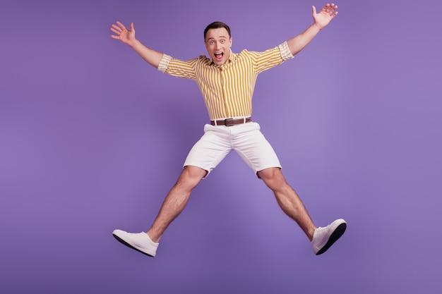 紫色の背景に狂ったびっくりした男のジャンプスターポーズダンスの肖像画