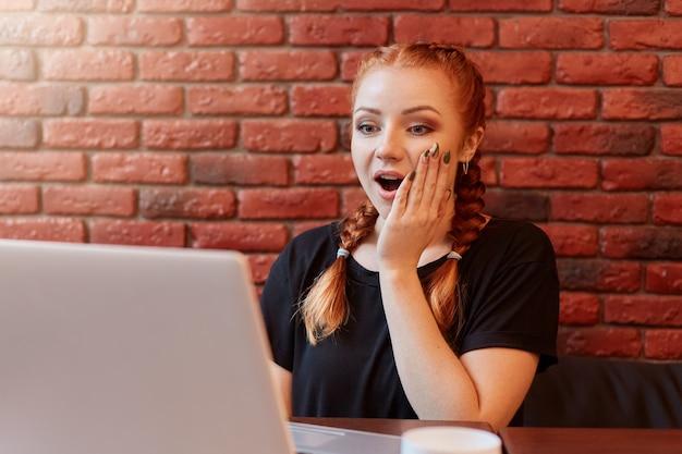 座って、開いた口とスペースにレンガの壁と大きな目で彼女のラップトップディスプレイを見ている狂気の美しい赤い髪の若い女性の肖像画