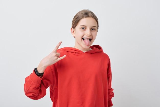 Портрет сумасшедшей крутой девочки-подростка в подтяжках, показывающей жест рога и высунувшей язык