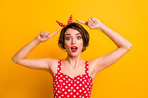 Портрет сумасшедшей смешной девушки указывает указательным пальцем на ее повязку в горошек, впечатленный криком, невероятно неожиданным, изолированным над блестящей цветной стеной