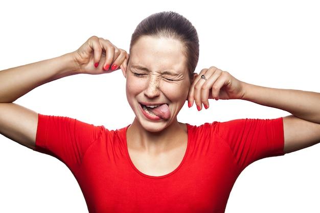 카메라를 보고 주근깨가 있는 빨간 티셔츠를 입은 미친 재미있는 여성의 초상화