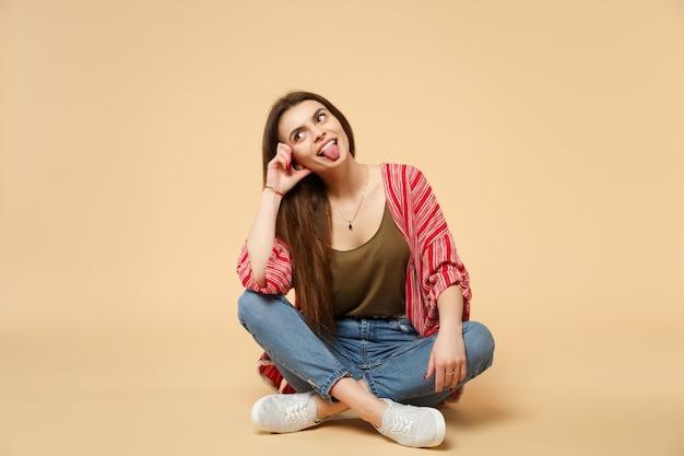 파스텔 베이지색 벽 배경에 고립된 혀를 보여주는 캐주얼 옷을 입은 미친 젊은 여성의 초상화. 사람들은 진심 어린 감정, 라이프 스타일 개념입니다. 복사 공간을 비웃습니다.