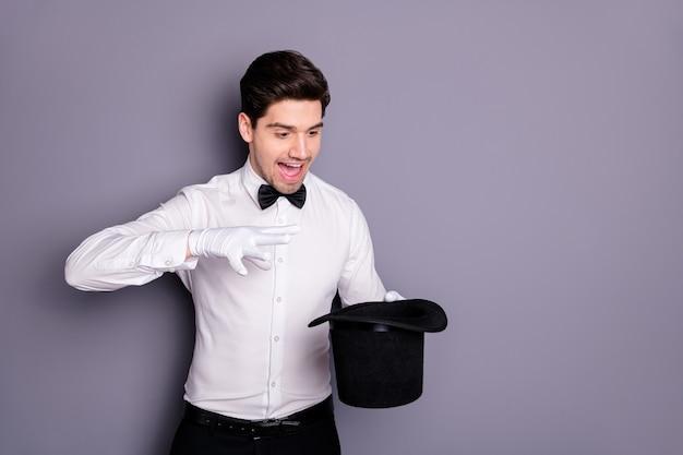 Портрет сумасшедшего волшебника, держась за руку, черная цилиндрическая шляпа, заставляющая заклинать абракадбру, развлекать публику цирка, носить официальную одежду, изолированную над серой стеной