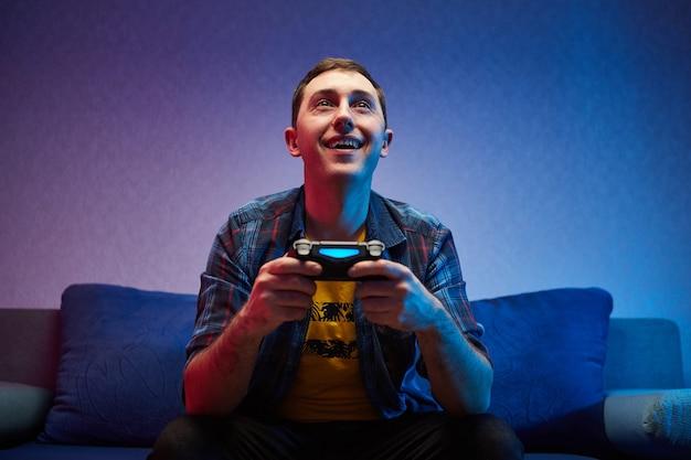 クレイジーな遊び心のあるゲーマーの肖像画、ソファに座って、コンソールゲームパッドを手に持って屋内でビデオゲームを楽しんでいる少年。家で休んで、素晴らしい週末を過ごしましょう
