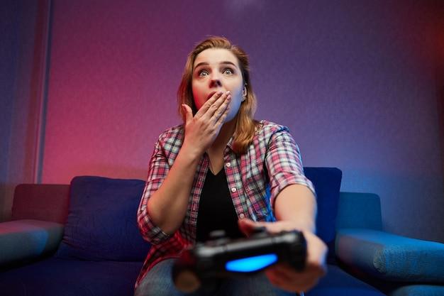 クレイジーな遊び心のあるゲーマーの肖像画、ソファに座って、コンソールゲームパッドを手に持って屋内でビデオゲームを楽しんでいる女の子。家で休んで、素晴らしい週末を過ごしましょう