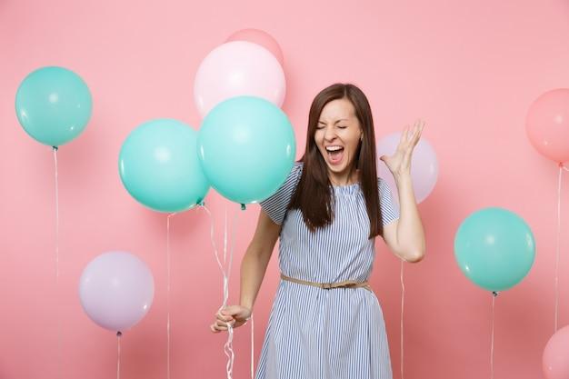 밝은 분홍색 배경에 화려한 공기 풍선을 들고 비명을 지르는 파란색 줄무늬 드레스를 입고 눈을 감고 미친 여자의 초상화. 생일 휴가 파티, 사람들은 진심 어린 감정 개념입니다.