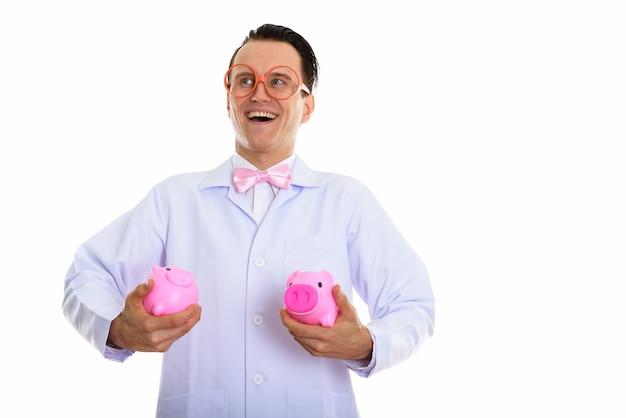 Портрет сумасшедшего доктора молодого человека, играющего с копилкой