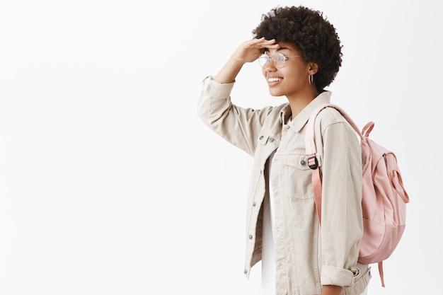 Портрет творческой и эмоциональной стильной темнокожей женщины с афро-прической, которая поворачивается налево и смотрит вдаль, положив руку на лоб, позирует с рюкзаком