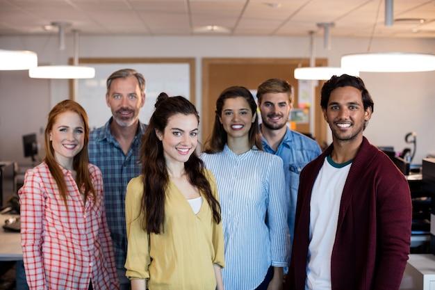 사무실에서 함께 서있는 창조적 인 비즈니스 팀의 초상화