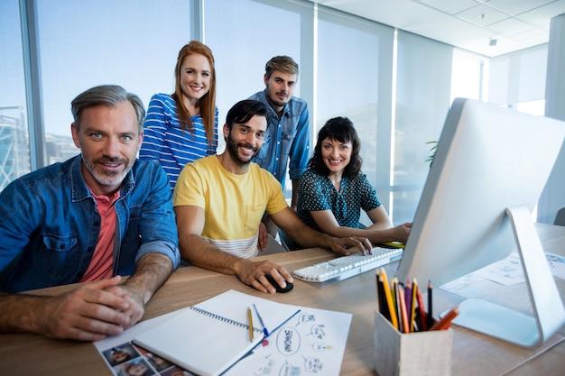 사무실에서 데스크톱 pc에서 함께 작업하는 창의적인 비즈니스 팀의 초상화