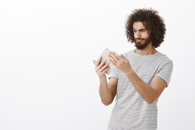 スタイリッシュなヘアカットとひげを持つ創造的なヒスパニック系男性デザイナーの肖像画、デジタルタブレットを押しながら画面に焦点を当てて見て、デザインを作成するアパートの計画を描く
