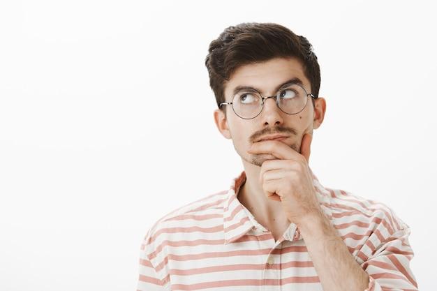 トレンディなメガネで創造的なスマートオフィスマネージャーの肖像画、あごを手でこすり、重要な式を考えたり覚えたりしながら脇を見つめ、灰色の壁を越えて科学の突破口を開く