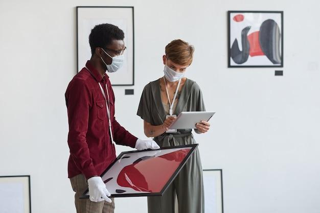 Портрет творческой татуированной женщины с помощью цифрового планшета во время планирования выставки в художественной галерее с афро-американским помощником,