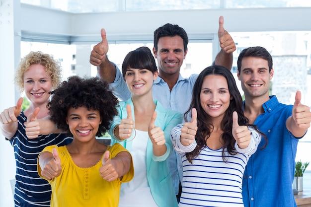Портрет творческой группы gesturing палец вверх