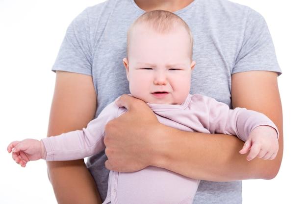 흰색 배경에 고립 된 아버지의 손에 우는 아기 소녀의 초상화