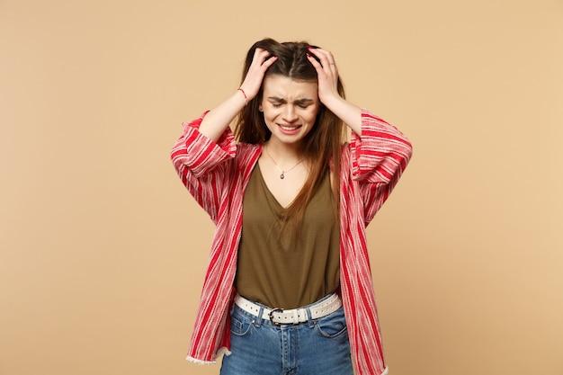 Портрет плача недовольной молодой женщины в повседневной одежде, положив руки на голову, изолированную на пастельных бежевых стенах в студии. люди искренние эмоции, концепция образа жизни. копируйте пространство для копирования.