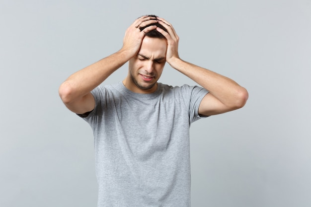目を閉じて頭に手を置いてカジュアルな服を着て泣いている不満の若い男の肖像画