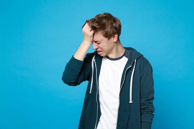 파란색 벽에 고립 된 머리에 손을 넣어 낮추고 머리와 캐주얼 옷에 우는 좌절 된 젊은 남자의 초상화. 사람들이 성실한 감정 라이프 스타일 개념.