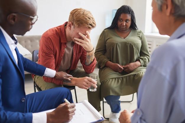 Портрет плачущего молодого человека, который делится своими проблемами во время встречи группы поддержки с людьми, сидящими в кругу и утешающими его