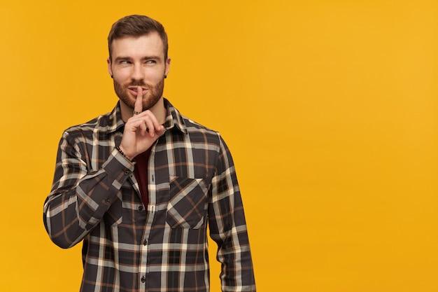 ブルネットの髪と剛毛を持つ狡猾な、大人の男性の肖像画。市松模様のシャツとアクセサリーを身に着けています。沈黙のサインを示しています。黄色い壁に隔離されたコピースペースで右を見る