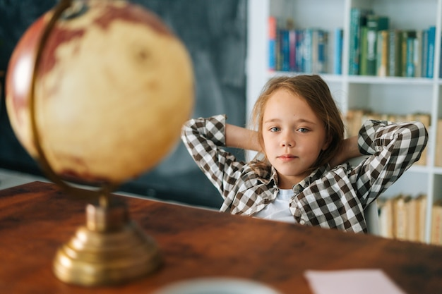 테이블 앞 머리 뒤에 손을 놓고 의자에 앉아 있는 호기심 많은 어린 소녀의 초상화