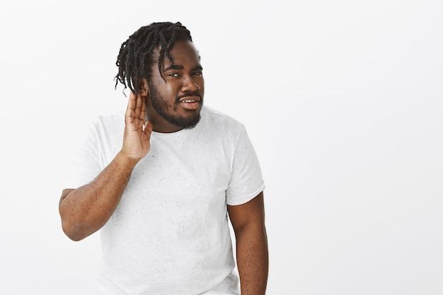 Портрет любопытного парня с косами позирует у белой стены