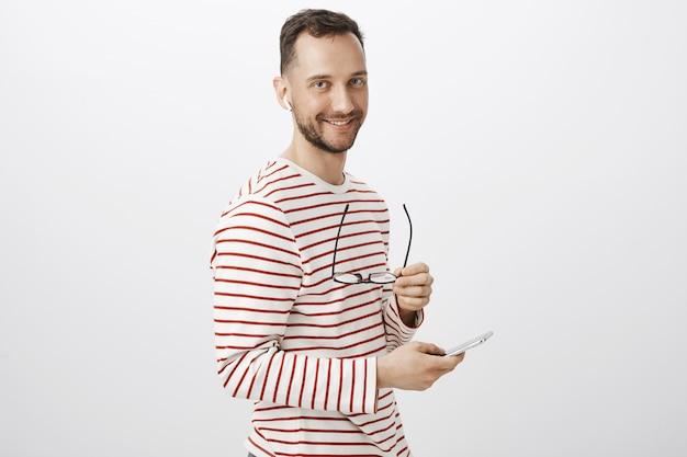 ストライプのプルオーバー、メガネを脱いでワイヤレスイヤホンでボーイフレンドの呼び出しを待っている好奇心が強いハンサムなヨーロッパのゲイの肖像画