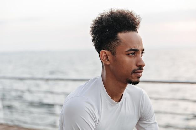 海の近くで目をそらしている白いスポーツの長袖t-shortの巻き毛のブルネットの浅黒い肌の思慮深い男の肖像画