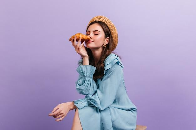 クロワッサンの香りを楽しむ巻き毛のブルネットの肖像画。紫色の壁にポーズをとってかわいいドレスと帽子の女の子。