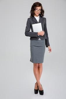 Портрет курчавой уверенной серьезной молодой красивой бизнес-леди в очках, держащей планшет