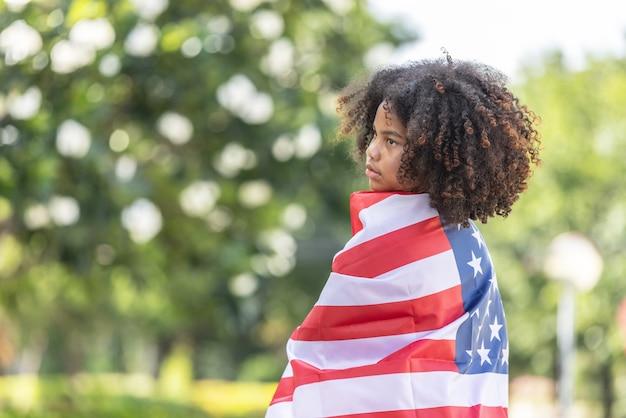 미국 국기와 함께 드레이프와 담요로 뒤덮인 곱슬머리 소녀 미국인의 초상화