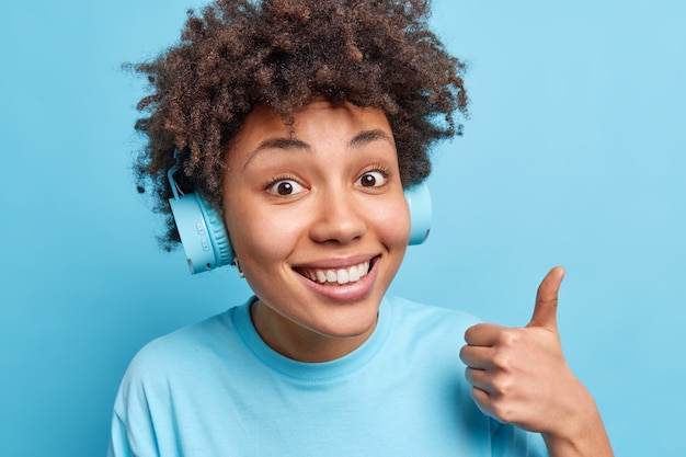 巻き毛のアフロアメリカンの肖像画は、ヘッドフォンを介してお気に入りのトラックを楽しんで音楽を聴き、親指を立て続け、青い壁に幸せに孤立した優れたサインの笑顔を示しています。ボディーランゲージの概念