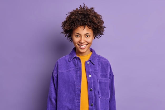 Портрет кудрявой красивой женщины улыбается, счастливо носит модную фиолетовую куртку в один тон с фоном, чувствует себя в восторге, позирует, радуется внутренним разговорам с коллегой. концепция положительных эмоций