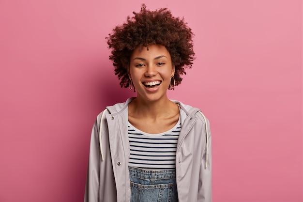 巻き毛の女性の肖像画はカメラで幸せに笑って、来る休日を喜ぶ