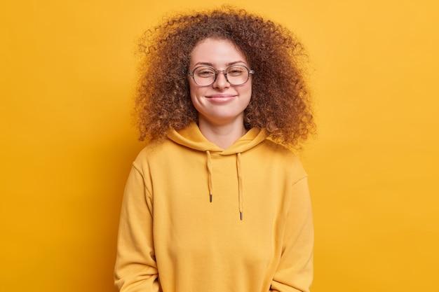 カジュアルなスウェットシャツと透明なメガネを着て心地よく笑顔の巻き毛の若い女性の肖像画は、賞賛されてうれしい鮮やかな黄色の壁の上に分離された表情を満足させています