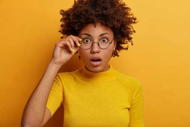 곱슬 머리 여자의 초상화는 무감각하고 안경의 테두리를 만집니다. 무료 사진