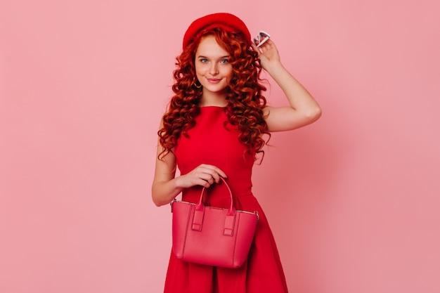 ピンクの空間に青い目をした巻き毛の女性の肖像画。笑顔でポーズをとってカメラを見ている真っ赤な服装の女性。