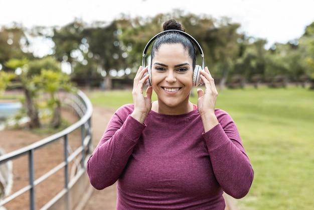 Портрет пышной женщины, слушающей музыку из плейлиста после пробежки на открытом воздухе