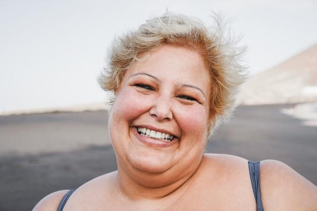 해변에서 비키니를 입고 웃는 매력적인 여자의 초상화-얼굴에 초점