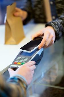 스마트폰을 사용하여 전자 리더기로 모바일 결제를 하는 고객의 초상화.