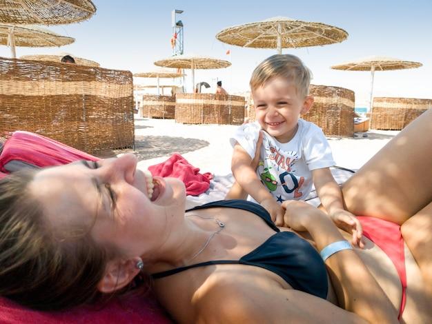 귀여운 3 살 소년 palying 및 해변에서 태양 침대에 누워 그의 어머니를 간지럼의 초상화. 가족 휴식과 여름 휴가 휴가 동안 해변에서 좋은 시간을 보내고