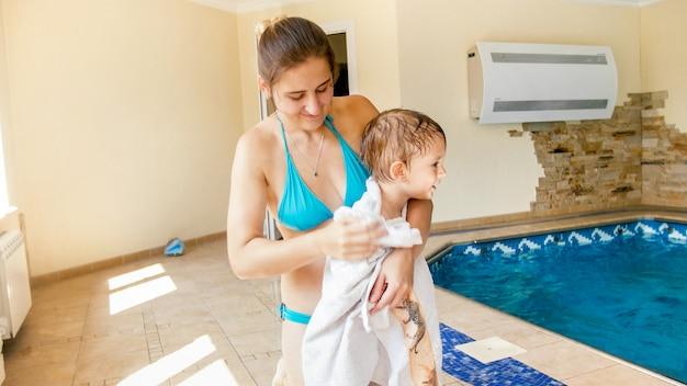 Портрет симпатичного 3-летнего мальчика в белом полотенце после плавания в бассейне и обучения плаванию