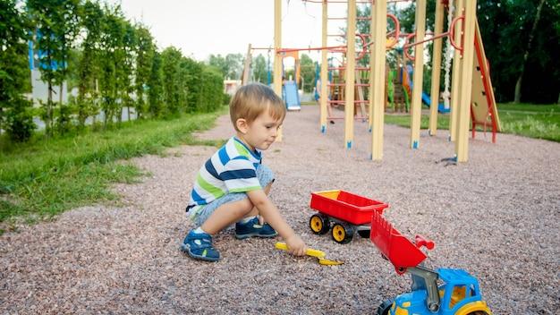 公園の遊び場に座って、カラフルなプラスチックのおもちゃのトラックで遊んでいるかわいい3歳の幼児の少年の肖像画。おもちゃで野外で遊んで楽しんでいる子供