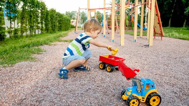 公園の遊び場に座って、カラフルなプラスチックのおもちゃのトラックで遊ぶかわいい 3 歳の幼児の少年の肖像画