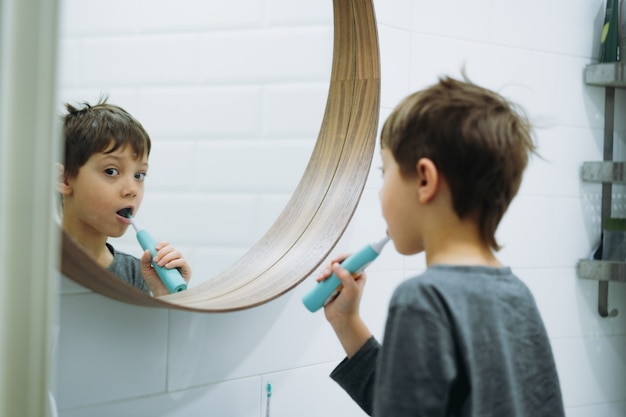 Портрет милого 6-летнего мальчика, чистящего зубы электрической щеткой в ванной комнате, глядя в зеркало