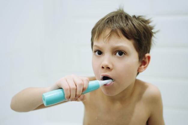 Портрет милого 6-летнего мальчика, чистящего зубы электрической щеткой в ванной комнате